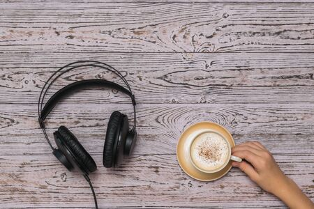 Hand holding a coffee Cup and black wired headphones on the wooden table. Coffee break during work. Reklamní fotografie