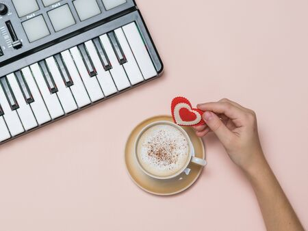 A hand holds a heart figurine near a coffee Cup and a music mixer. The process of creating music. Hobbies and recreation. The view from the top.