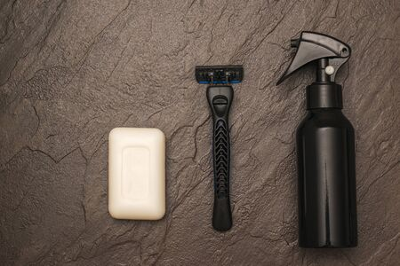 A man's razor, a piece of white soap and spray on a stone background. Set for care of a man's face. Flat lay.