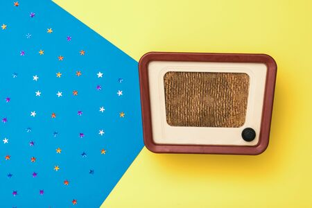 Vintage radio on a yellow and blue background with stars. Simulation of radio broadcasts. The view from the top.