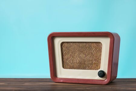 Vintage radio on a wooden table on a blue background. Radio engineering of the past time. Retro design.