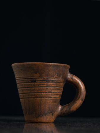Clay mug with handle on black background. Ancient pottery.