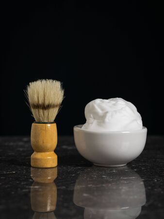 Shaving brush with a bowl of shaving foam on a stone background. Set for care of a man's face.