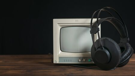 Black headphones with wire and retro monitor on wooden table on black background. Technique for sound and video reproduction.