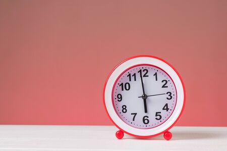 Red alarm clock on a white table on a red background. Classic analog clock.