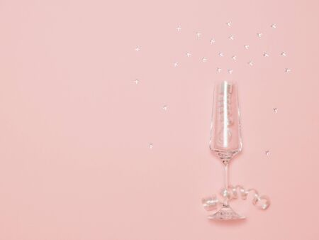 Elegant champagne glass with serpentine and luminous sequins on a pink background. Festive background with champagne glasses.