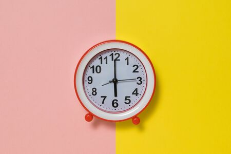 Clock with hands on a yellow and pink background.. Classic analog clock. Zdjęcie Seryjne