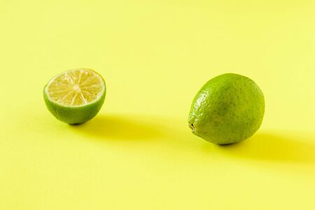 One whole lime and half on a yellow-green background. Citrus fruits for making a drink.