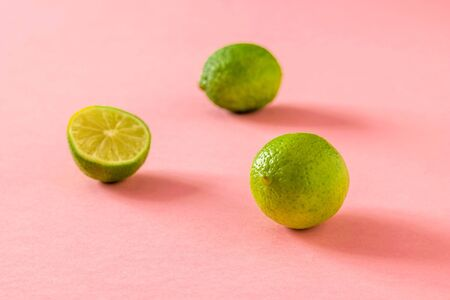 Ripe green limes on a pink background. Citrus fruits for making a drink.