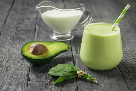 A glass of avocado and spinach smoothies with almond milk on a wooden table. Fitness product. Dietary sports nutrition.
