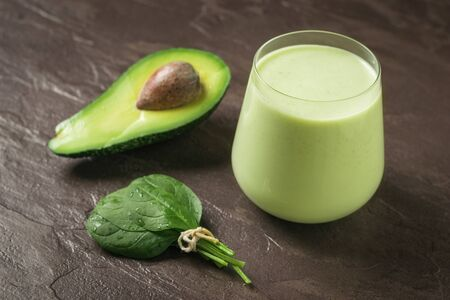 Bunch of spinach leaves, avocado and smoothies on a stone background. Fitness product. Dietary sports nutrition. 스톡 콘텐츠