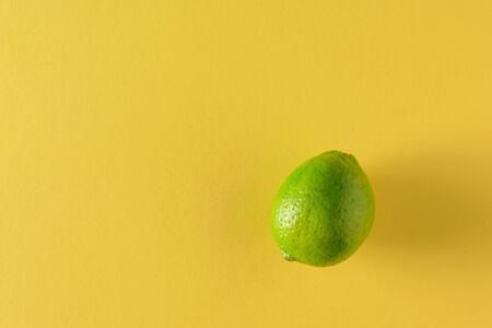 Lime green on a large yellow background. Citrus fruits for making a drink. Flat lay.
