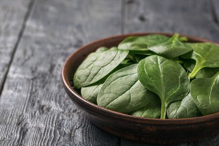 Bright fresh spinach leaves in a clay bowl on a wooden table. Food for fitness. Vegetarian food.