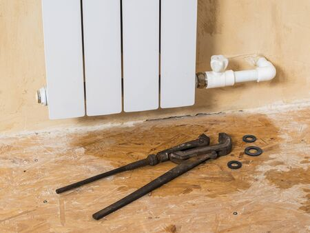Repair tools and rubber gaskets for radiators near a leaking heating system. Accident of the heating system of a private house. Heating radiator.