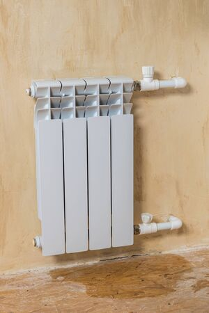 Leaking radiator of four sections in a private house. Accident of the heating system of a private house. Heating radiator.
