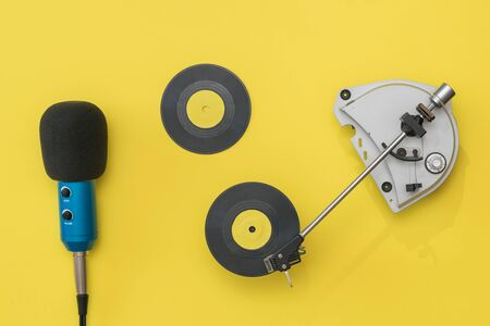 Vinyl record player, microphone and two discs on a yellow background. Retro technique for playing music.