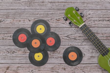 Multicolored vinyl discs and a green guitar on a wooden table. Retro technique for playing music.