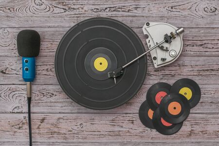 Vinyl discs, a player and a microphone on a wooden background. Retro technique for playing music. Stockfoto