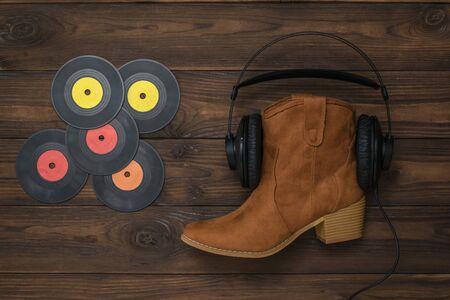 Vinyl discs, boots, headphones on a wooden background. Concept of folk music.