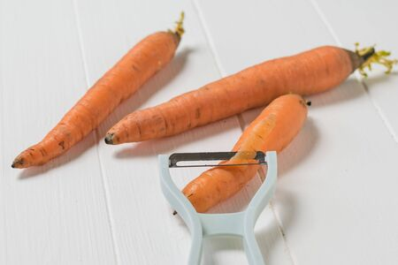 The peeler cuts the top layer off the carrots. Cleaning carrots with a special knife.