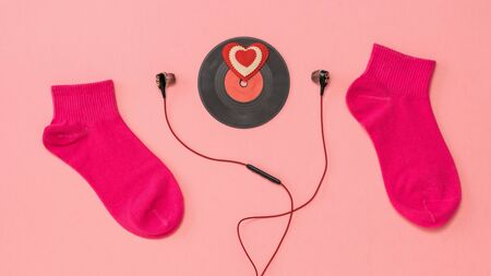 Two sporty red socks, red headphones, and a red vinyl disc on a pink background. The concept of music and sports. Flat lay.