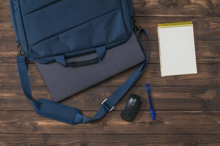 A blue bag with a protruding laptop, a mouse, and a Notepad on a wooden table. Accessories for study, business and work.