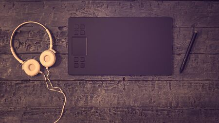 A tinted image of a graphics tablet with white headphones on a wooden background. A device for working in image editors.