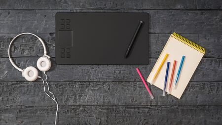 A graphic tablet, white headphones, and a set of markers on a wooden table. A device for working in image editors.