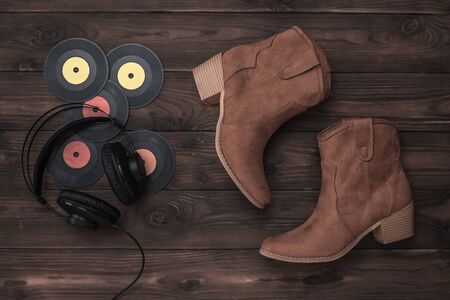 Tinted image of headphones, vinyl discs and suede boots on a wooden background. Concept of folk music.
