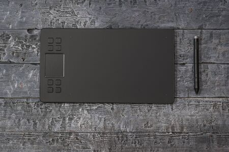 Classic graphic tablet and pencil on a wooden background. A device for working in image editors.