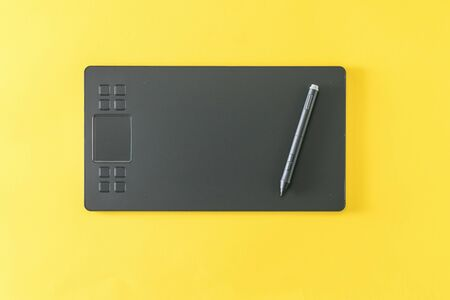 Graphic tablet with a pencil on a bright yellow background. A modern device for working with image editors.