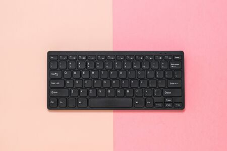 Black wireless keyboard on pink and red background. Peripheral devices for computers.