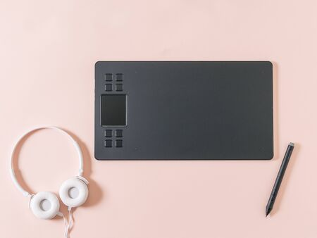 Graphic tablet, pencil and white headphones on a pink background. A device for working in image editors.