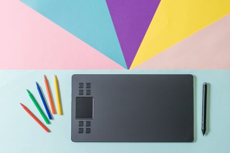 A graphic tablet with a pencil and a set of markers on a multicolored background. A modern device for working with image editors.