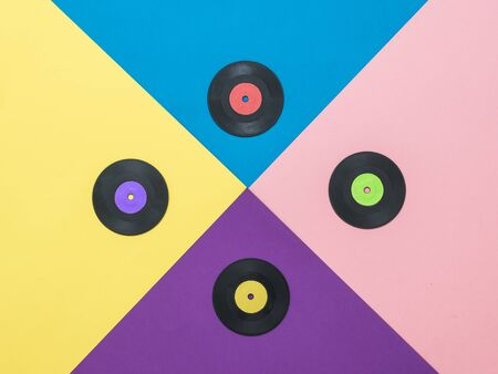 A set of multi-colored vinyl discs on a multi-colored background. Collage of vinyl discs. Abstract background. Flat lay.