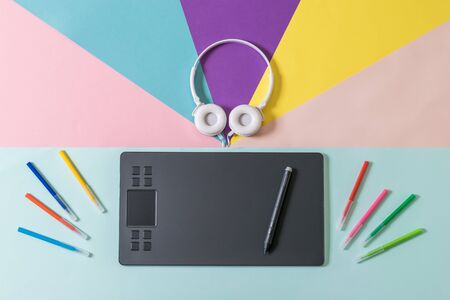 Scattered markers, white headphones, and a graphic tablet on a multicolored background. A device for working in image editors.