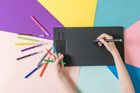 Hands with a set of colored markers and a graphic tablet on a multi-colored paper background. A modern device for working with image editors.