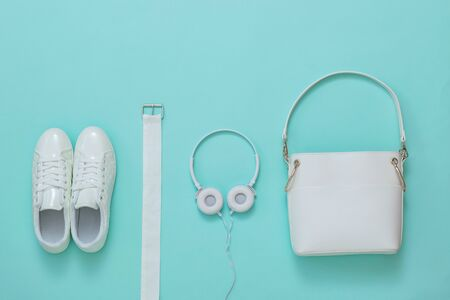 White sneakers, white headphones, white belt and white bag on a light background. Fashion women's accessories. Flat lay.