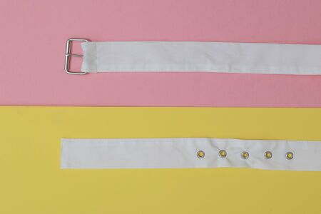Two white belts on a red and yellow background. Women's accessory. The concept of differentiation. 스톡 콘텐츠