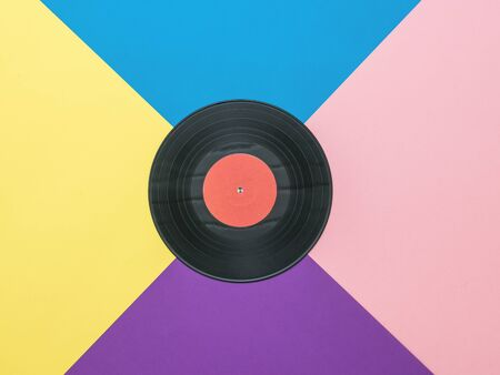 A large vinyl disc on a multicolored abstract background. Collage of vinyl discs. Abstract background. Flat lay.