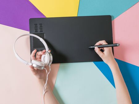 Hands of a child with headphones, a graphic tablet and a pencil on a background of colored paper. A device for working in image editors.
