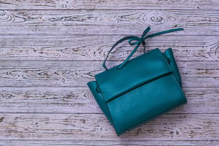 Leather women's bag in turquoise color on a wooden background. Modern women's leather accessory.