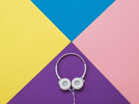 White headphones on an abstract background of four colors. Mobile audio playback equipment.