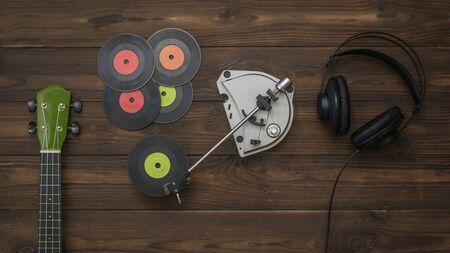 Headphones, guitar and player with vinyl discs on a wooden background. Retro technique for playing music. Standard-Bild