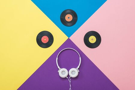 White headphones with wire and vinyl discs on an abstract background. Retro technique for playing music.