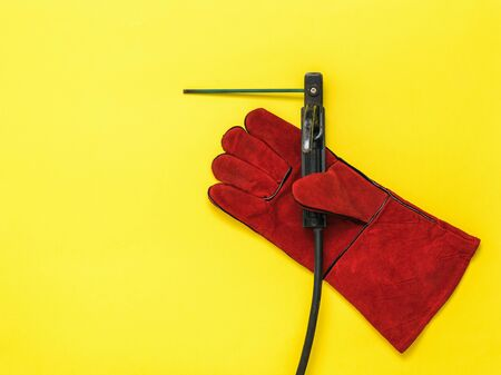 Red welder's glove with a welding electrode. Protective accessory for welding operations.