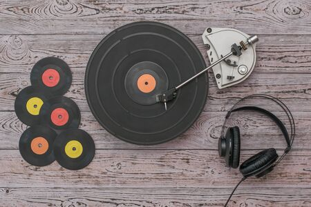 A set of vinyl discs, headphones and a player on a wooden background. Retro technique for playing music.