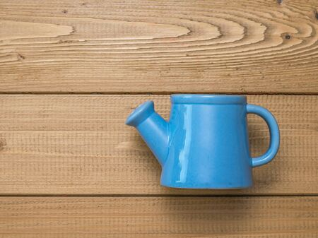 Blue watering can for plants on a wooden background. A tool for tillage.
