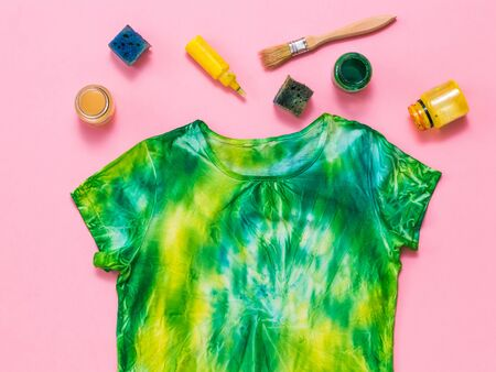 Yellow and green tie dye t-shirt with colors on a red background. White clothes painted by hand. Flat lay. Place for text.