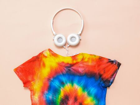 A bright tie dye t-shirt with headphones on a pastel background. White clothes painted by hand. Flat lay. Place for text. Pastel color.